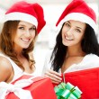 Young happy girls in Christmas hats.Standing together indoors and holding b — Stock Photo
