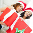 Young happy girls in Christmas hats.Standing together indoors and holding b — Foto de Stock