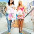 Closeup of two attractive happy girls out shopping. They are mov - Stock Photo