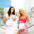 Stock Photo: Closeup of two attractive happy girls out shopping. They are mov