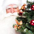 Christmas theme: Santa Claus holding christmas tree and his bag full of gif - Stock Photo