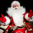 Santa sitting with a sack indoor at dark night room — Stock Photo