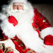 Santa sitting with a sack indoor at dark night room - Stock Photo