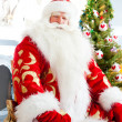 Santa sitting at the Christmas tree, fireplace and looking at ca — Stock Photo #7558393