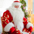 Santa sitting at the Christmas tree, fireplace and looking at ca — Stock Photo #7558395