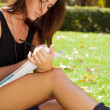 Portrait of a beautiful young female student sitting outdoor at - Stock Photo
