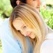 Portrait of love couple embracing outdoor in park looking happy — Stock Photo