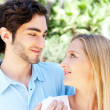 Portrait of love couple embracing outdoor in park looking happy — Stockfoto