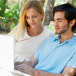 Young couple working on laptop and smiling while sitting relaxed — Stock Photo