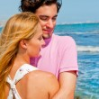 Portrait of young couple in love embracing at beach and enjoying - Stock Photo
