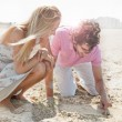 Couple in love drawing a heart in the sand while relaxing at bea — Stock Photo #7558774