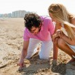 Couple in love drawing a heart in the sand while relaxing at bea — Stock Photo