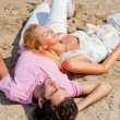 Young couple relaxing on sand at beach and daydreaming with thei — Stockfoto