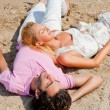 Young couple relaxing on sand at beach and daydreaming with thei — 图库照片