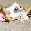 Young couple lying together on a sand by sea and looking to a sk — Stock Photo