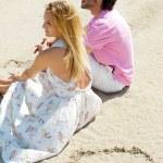 Porträt des jungen Paares zusammensitzen auf Sand am Strand und l — Stockfoto