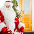 Santa sitting at the Christmas tree, fireplace and looking at ca — Stock Photo #7558900