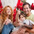 Stock Photo: Happy family embracing and sitting on the floor in front of Chri