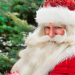 Santa Claus portrait smiling against christmas tree outdoor in s — Stock Photo #7559001