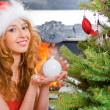 Christmas woman near a Christmas tree holding Christmas toy whil — Stock Photo