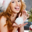 Stock Photo: Christmas woman near a Christmas tree holding Christmas toy whil