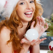 Christmas woman near a Christmas tree holding Christmas toy whil — Stock Photo #7559055