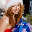 Christmas woman near a Christmas tree holding big gift box while — Stock Photo #7559065