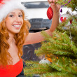 Christmas woman near a Christmas tree holding Christmas toy whil — Stock Photo #7559072
