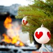 Christmas baubles against burning flame in fireplace on christma — Stock Photo