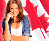 Portrait of a pretty young woman against a Canadian flag , smili — Stock Photo
