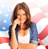 Portrait of a pretty young woman ôïôøòûå an American flag , smil — Stock Photo
