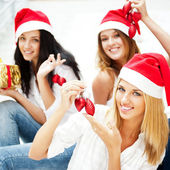 Group of three beautiful girls sitting on stairs at shopping mall hall wear — Stock Photo