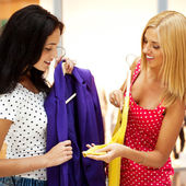 Group of two beautiful shopping women trying on clothes at shopp — Stock Photo