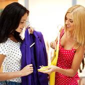 Gruppo di due belle donne dello shopping cercando sui vestiti a shopp — Foto Stock