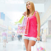 Portrait of a smiling young woman holding a shopping bags at a s — Stock Photo