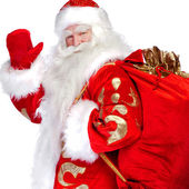 Santa Claus standing up on white background with his bag full of — Stock Photo