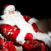 Santa sitting with a sack indoor at dark night room — Stock Photo