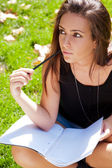A shot of an caucasian student studying on campus lawn — Stock Photo