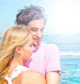 Portrait of young couple in love embracing at beach and enjoying — Foto de Stock