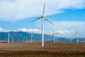 Wind power station - wind turbine against the blue sky — Stock Photo