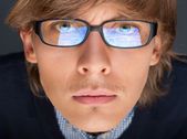 Satisfied young man with glasses looking at camera like at lapto — Stock Photo