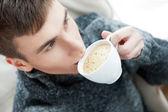 Retrato de un hombre joven bebiendo café sentado en varios — Foto de Stock
