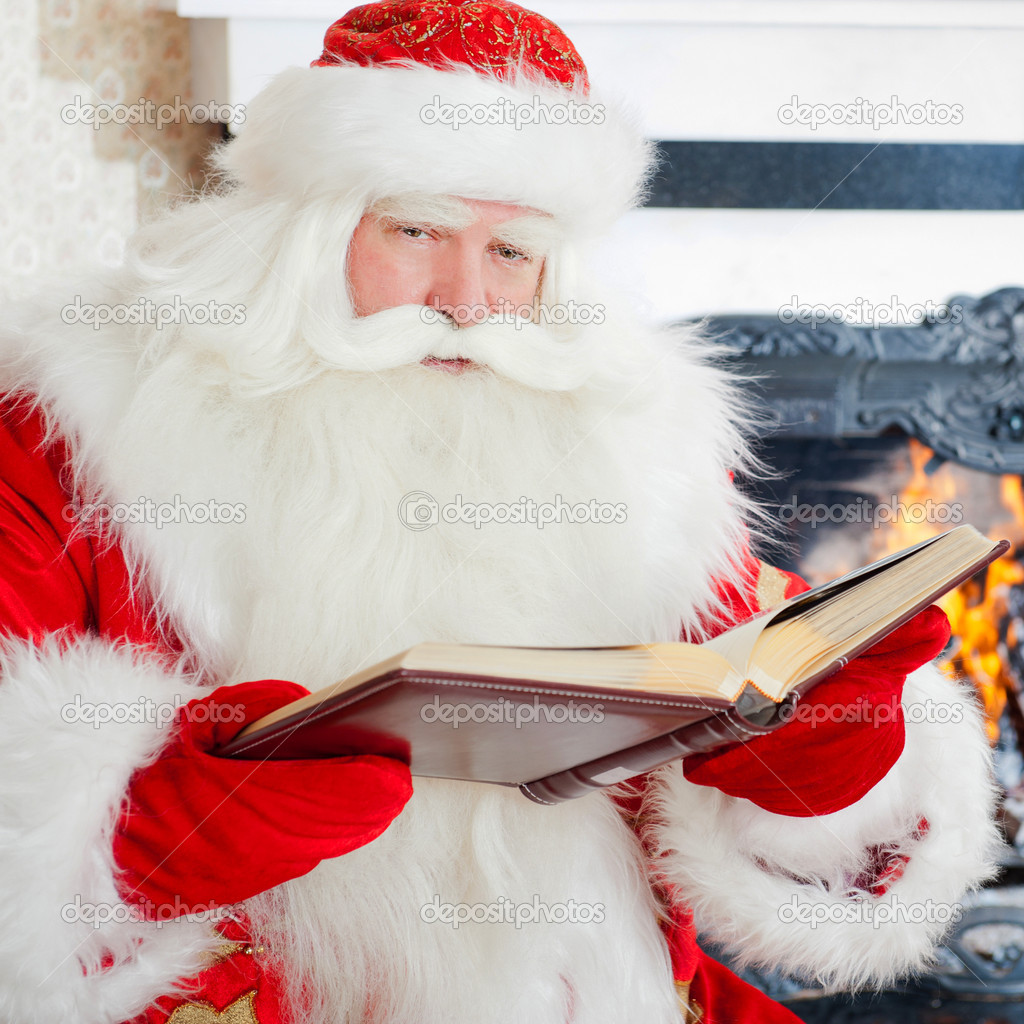 Santa sitting at the Christmas tree, fireplace and reading a book — Stock Photo #7558397