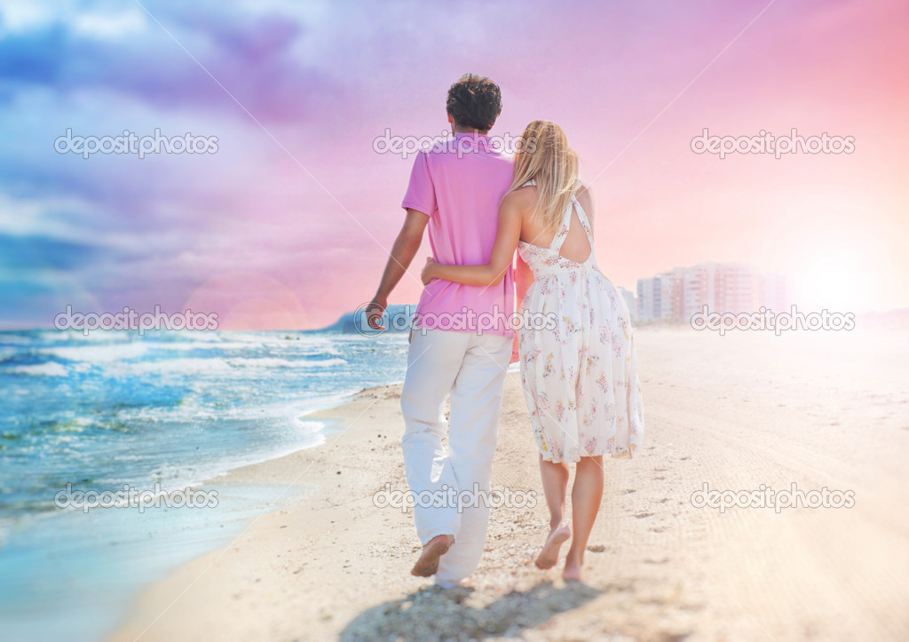Idealistic poster for advertisement. Couple at the beach holding hands embracing and walking. Sunny day, bright colors. Photo from behind.  Europe, Spain, Costa    #7558729
