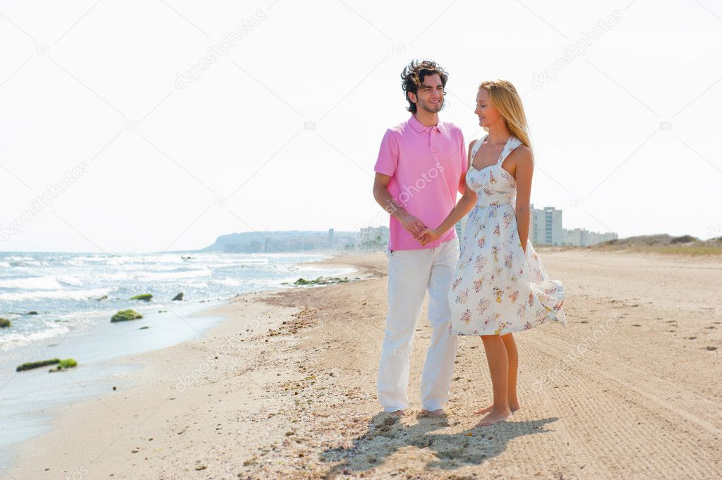 Couple at the beach holding hands and walking. Sunny day, bright colors. Europe, Spain, Costa Blanca — Stock Photo #7558734