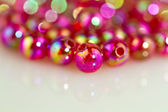 Red beads white surface background II — Stock Photo
