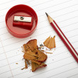 Sharpened pencil next to the sharpener and shavings. — Stock Photo