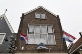 Holland, Volendam, old stone house and Holland flags — Стоковое фото