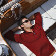 Italy, Tuscany, young sailor is resting on a wooden sailing boat - Lizenzfreies Foto