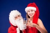 Santa Claus with sexy girl in Santa hat. — Stock Photo